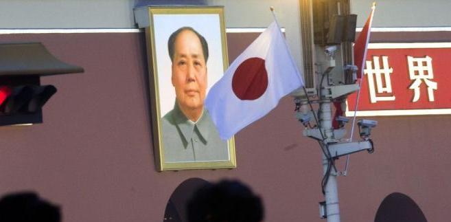 Japońska flaga na Placu Tienanmen w Pekinie na tle portretu twórcy Chin ludowych Mao Zedonga