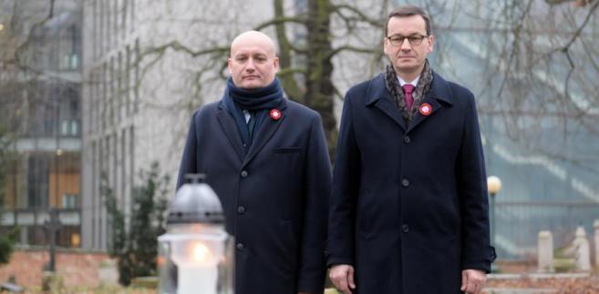 Premier RP Mateusz Morawiecki i wojewoda wielkopolski Zbigniew Hoffmann składają kwiaty na mogile generała Stanisława Taczaka na Cmentarzu Zasłużonych Wielkopolan.