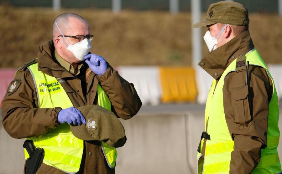 Funkcjonariusze służb granicznych podczas kontroli sanitarnej pasażerów autobusów wjeżdzających do Polski